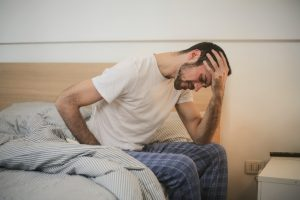 Man sitting next to bed with head hurting