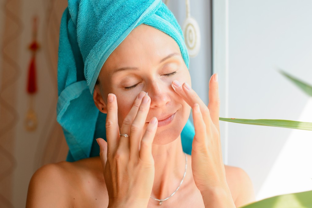 Closed eyes women touching face after shower